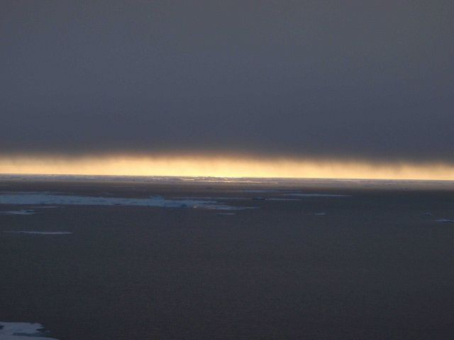 In a polynya looking towards sunlight playing on water while a blanket of cloud totally obscures the sun. Picture