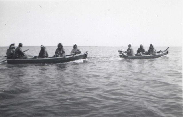 Two boats carrying native Americans - first boat equipped with outboard motor towing the second boat. Picture
