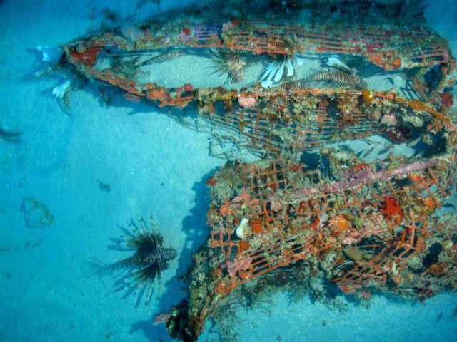 Marine debris - broken deserted fish trap on sand bottom Picture