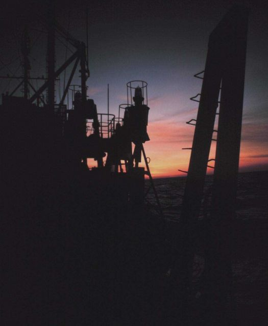 Sunset with tops of lighted buoys silhouetted during Gulf Stream eddy studies. Picture