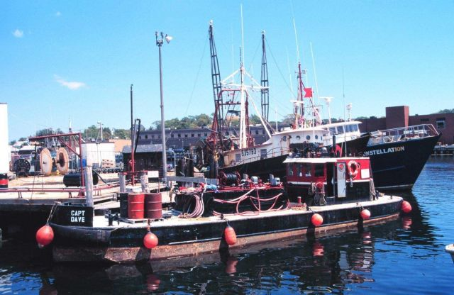 Trawlers tied up behind a small barge Picture