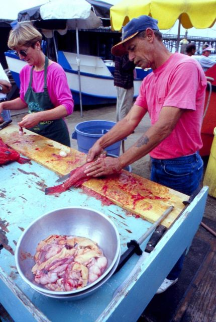 Family affair fish market as husband and wife fillet fish. Picture