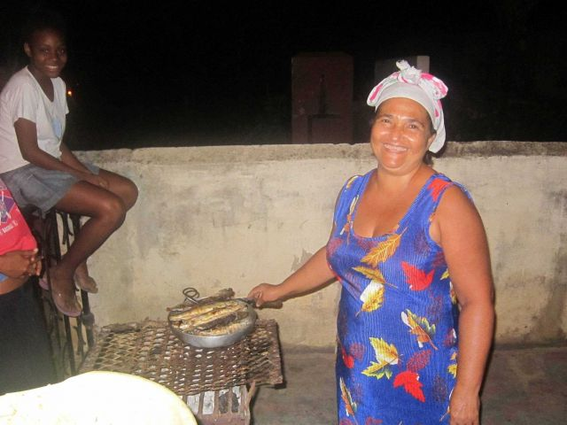 Maria, local Sao Tomean buisness woman, cooking flying fish at restaurant out of her home. Picture