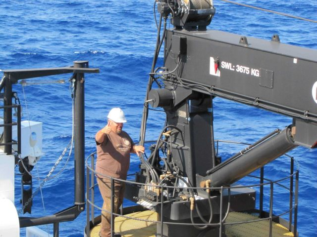 Lead fisherman operating crane communicating with hand signals. Picture