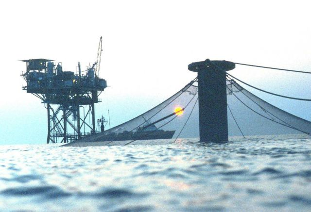 Sunset view of an offshore cage in the Gulf of Mexico near an oil rig. Picture