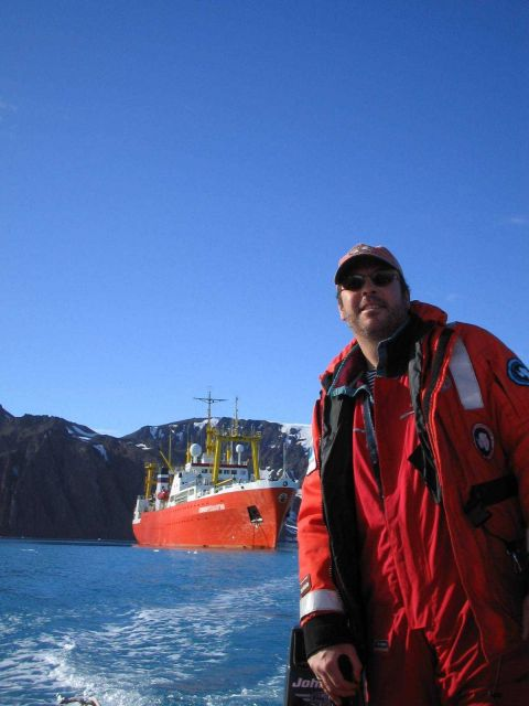 AMLR scientist Adam Jenkins drives a Zodiac near the R/V Yuzhmorgeologiya. Picture