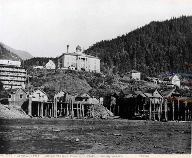 Indian village on stilts on tidal flats with United States Courthouse on hill above. Picture