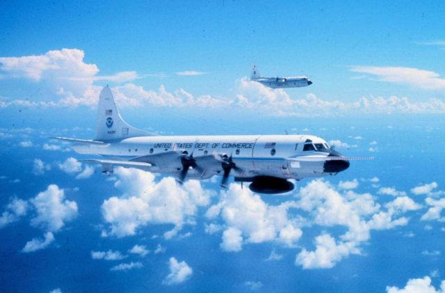 Closeup of NOAA P-3 N42RF in flight; NOAA C-130 N6541C flying outboard of P-3. Picture
