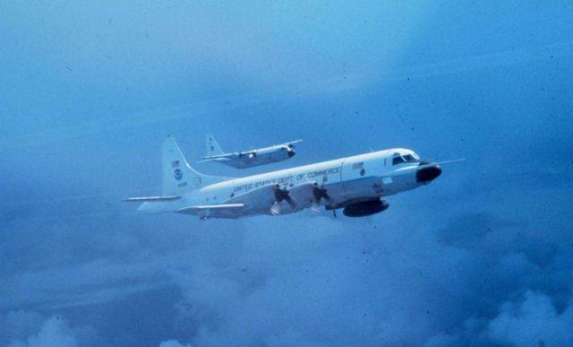 NOAA P-3 N42RF in flight; NOAA C-130 N6541C flying outboard of P-3. Picture