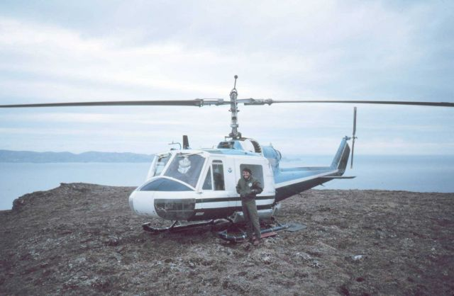 Helicopter mechanic alongside Bell helicopter supporting geodetic operations on the Alaska Peninsula. Picture