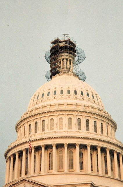 Looking SW from ground at scaffolding surrounding the top of the Capitol Building with the Statue of Freedom removed. Picture