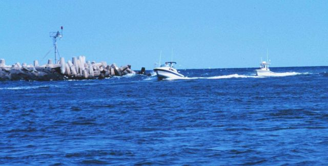 Recreational fishing boats passing the jetties at Manasquan Inlet Picture
