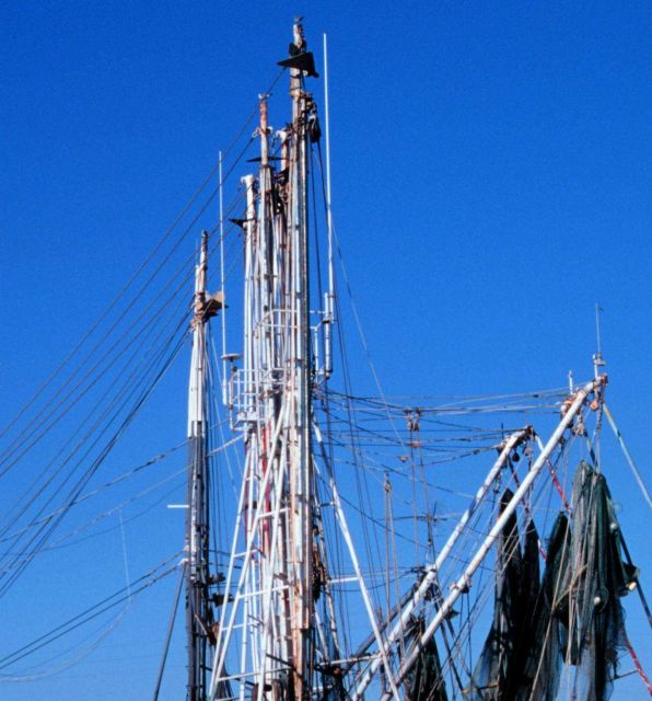 Masts and booms of shrimp boat with nets drying. Picture