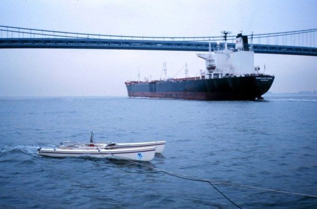 An outbound ship passes under Verrazano Narrows Bridge as a NOAA modified catamaran takes mobile current profiles with an acoustic data collection pla Picture
