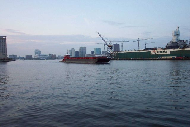 Tug pushing barge down the Elizabeth River with Norfolk skyline and shipyard in picture. Picture