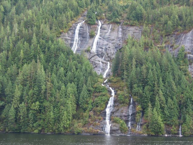 Dancing waterfalls, grey cliffs and evergreens at the edge of the sea. Picture
