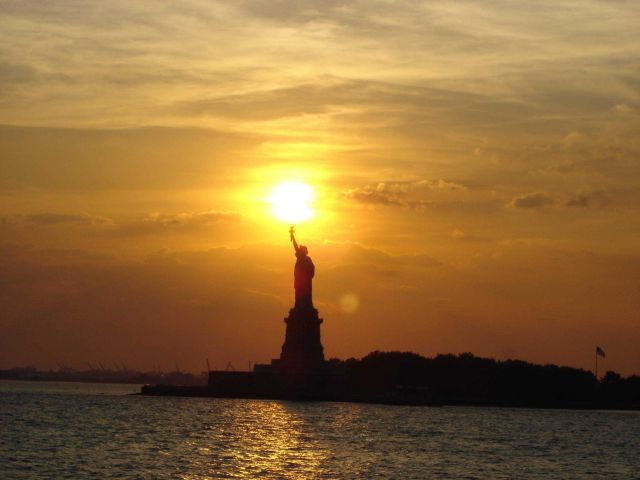 The Statue of Liberty at sunset holding the torch of freedom aloft. Picture