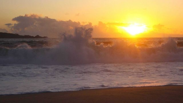 Waves and sunset over Carmel Bay with Point Lobos in the left center. Picture