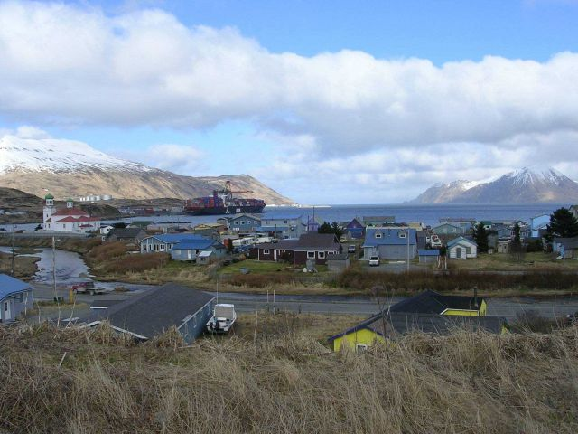 Residential district of Dutch Harbor with the old Russian Orthodox Church and the American President Lines container dock in the middle distance Picture