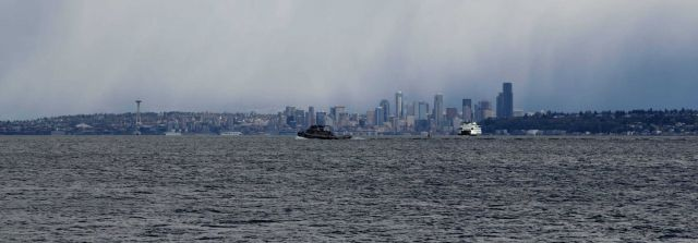 Seattle skyline from Puget Sound with ferryboat and tugboat. Picture