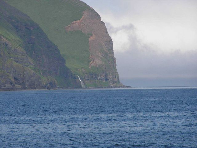 A waterfall rushing to the sea between impressive Aleutian cliffs. Picture