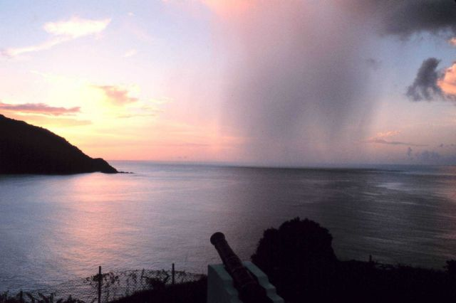 A rain shaft pierces a tropical sunset as seen from Man-of-War Bay. Picture