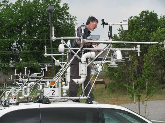Sherman Frederickson, NSSL, woring on the instrument rack on top of a mobile mesonet vehicle. Picture