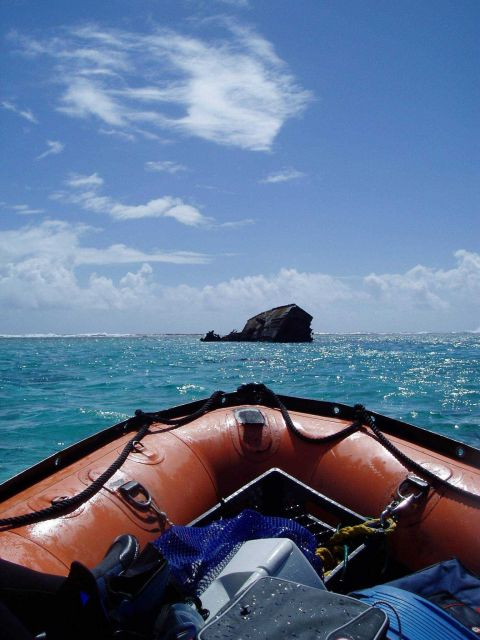 Approaching the remains of a shipwreck in a small boat off the NOAA Ship HI'IAlAKAI. Picture