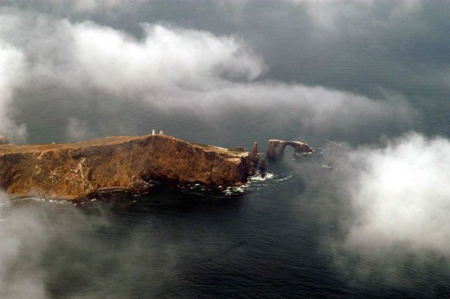 Anacapa Island and lighthouse through the clouds. Picture