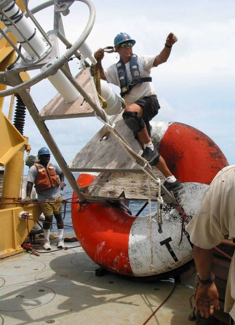 NOAA Ship KA'IMIMOANA Chief Bosun Roger Stone reaches for the crane hook so that the recovered TAO buoy can be moved off the fantail. Picture