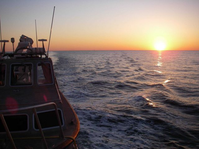 Looking astern at sunset from NOAA Ship THOMAS JEFFERSON over survey launch in davits. Picture