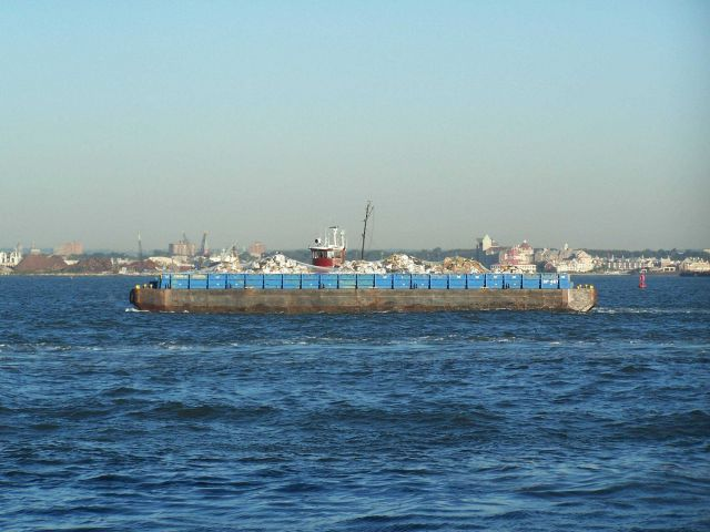 Tug towing garbage barge alongside Picture