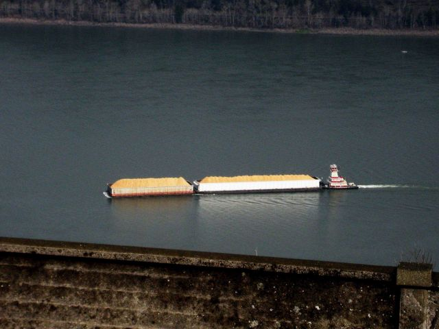 A push boat on the Columbia River pushing what appears to be loaded barges of sand. Picture