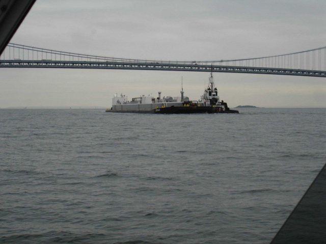 Tug pushing barge ahead under Verrazano Narrows Bridge. Picture