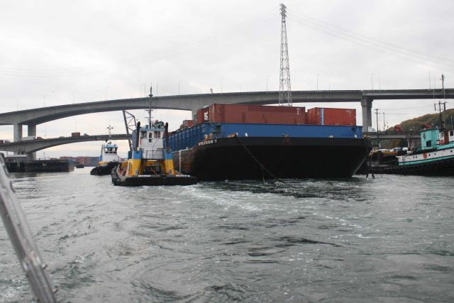 Container barge WESTERN 7 being maneuvered through narrow waterways. Picture