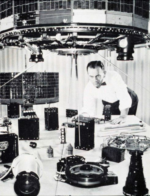 Scientist inspecting early TIROS satellite components Picture