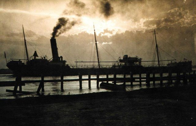 Tanker passing the jetties at sunset Picture