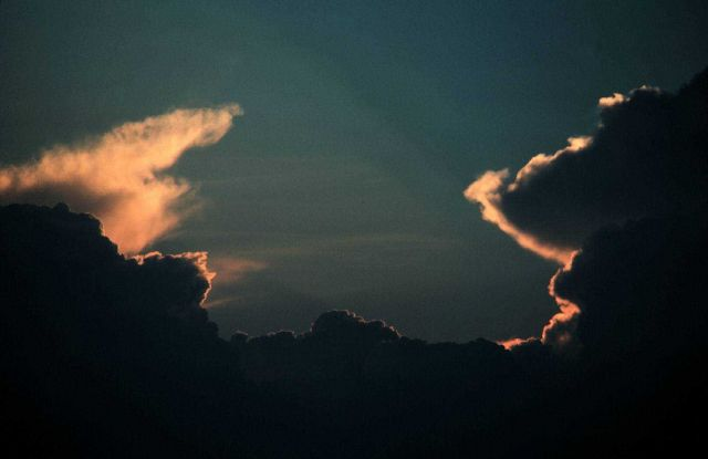 Twin cumulonimbus clouds with anvils at sunset Picture