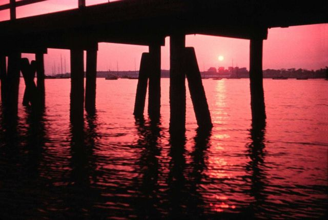 Sun setting with reflections through pier legs Picture