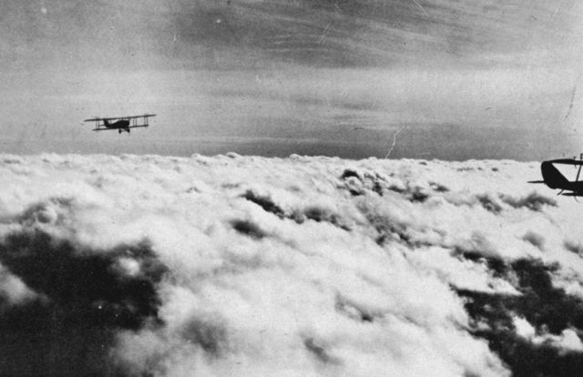 Military aircraft flying over layer of strato-cumulus; cirro-stratus above Picture