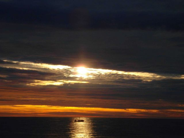 A fishing boat captured in a beam of light at sunrise. Picture