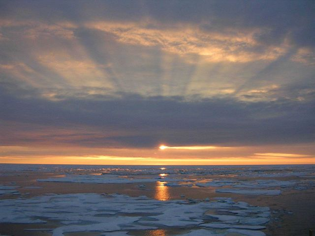 Sunset over the Arctic ice with shadow bands above and reflections on the water below. Picture