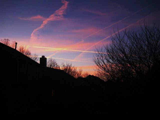 Criss-crossing jet contrails make a rhomboidal pattern at sunset. Picture