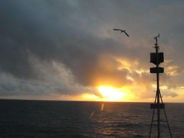 A blazing sunset at sea as the NOAA Ship HI'IALAKAI is seemingly led to the west by a booby flying over the jackstaff. Picture