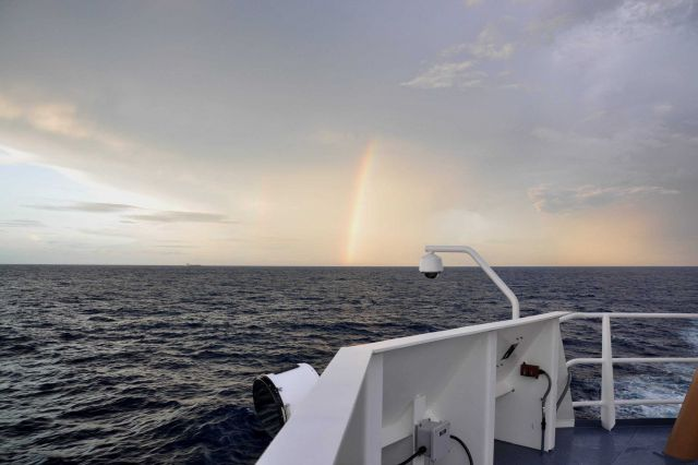 Rainbow at sunset with a small cargo ship in the distance. Picture
