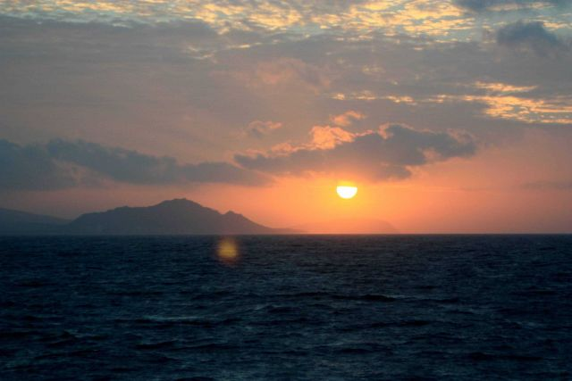 Sun setting over Tahiti on departure from Papeete. Picture