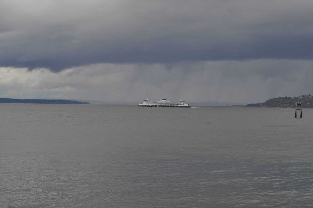 A ferry boat crossing Puget Sound with rain falling in the distance. Picture