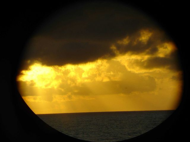 A golden sunset seen through a MILLER FREEMAN porthole. Picture