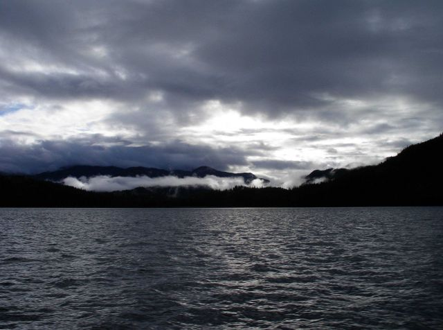 Clouds over head and fog filled valleys give a lead gray cast to Alaskan waters. Picture
