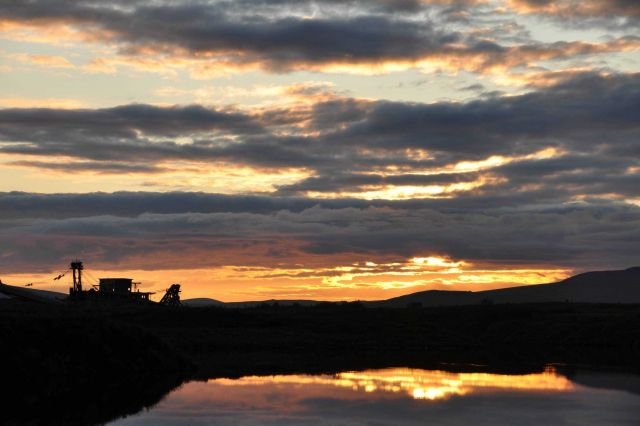 Sunset and clouds reflecting off water accented by the silhouette of an ancient gold dredge. Picture
